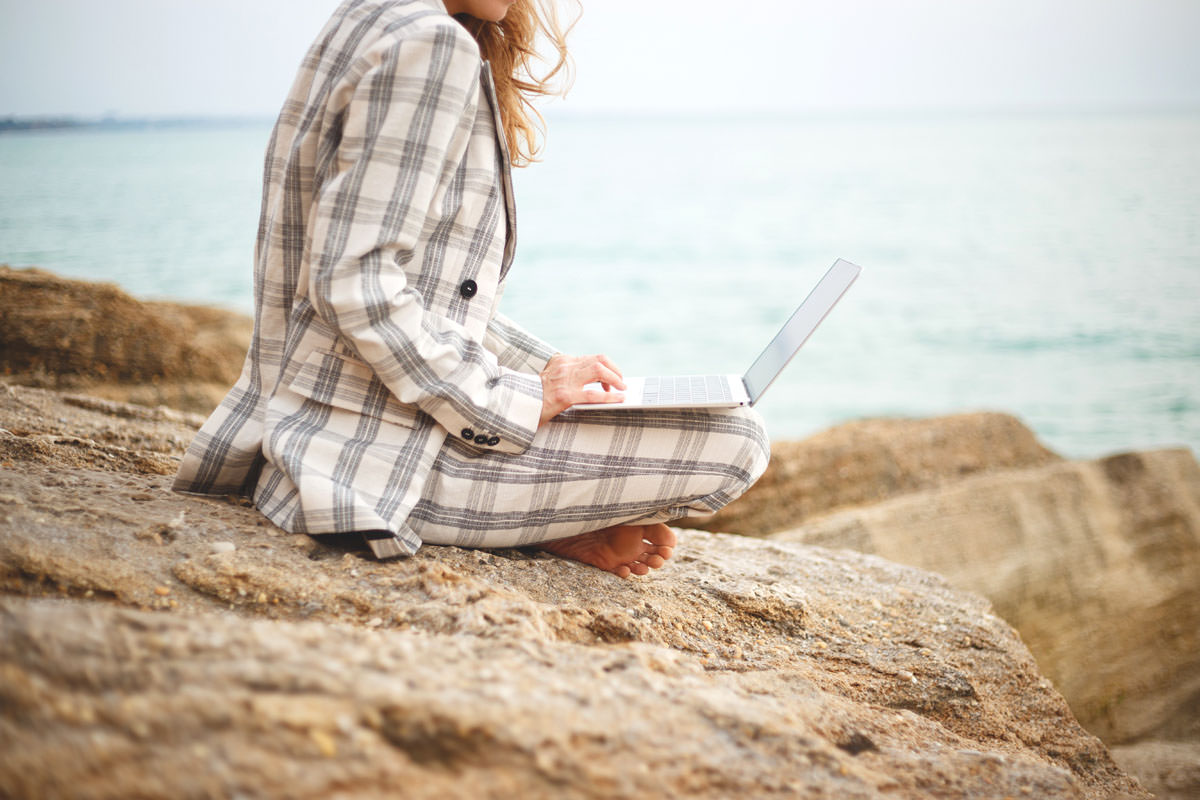 girl with a laptop by the sea. remote work concept